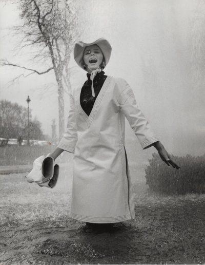 Jill Kennington wearing white PVC rain tunic and hat. Photograph by  John Cowan, 1963 Courtesy of Fashion Museum Bath/Image © John Cowan Archive