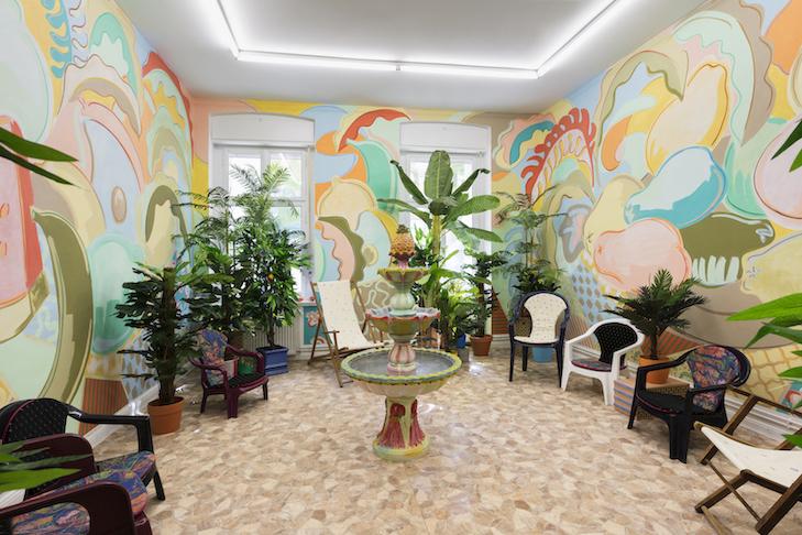 Sol Calero El patio de Espino, 2019 Acrylic and pastel on wall, plastic plants, chairs, bricks, vinyl floor, fountain Dimensions variable // Courtesy the artist and ChertLüdde, Berlin
