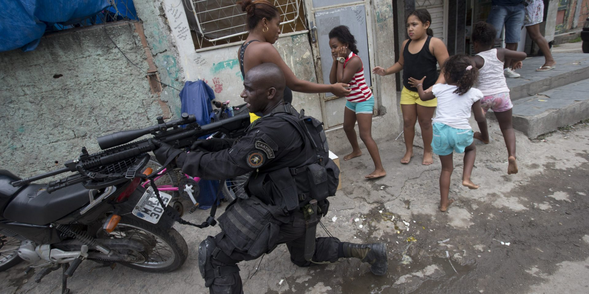 "Special Police Operations Battalion (BOPE) officer takes position while residents run for cover during an operation in the Mare slum complex, ahead of its ""pacification,"" in Rio de Janeiro, Brazil, Wednesday, March 26, 2014."